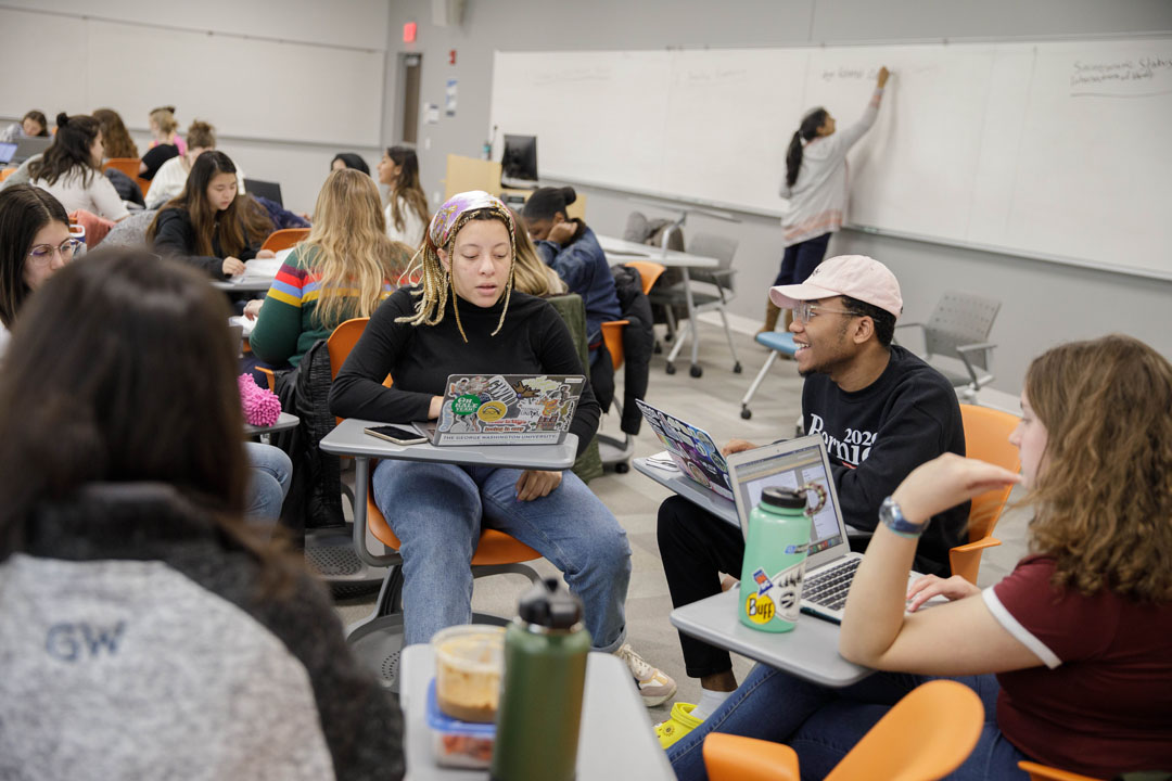 A group of students talk while sitting at desks with a professor behind them