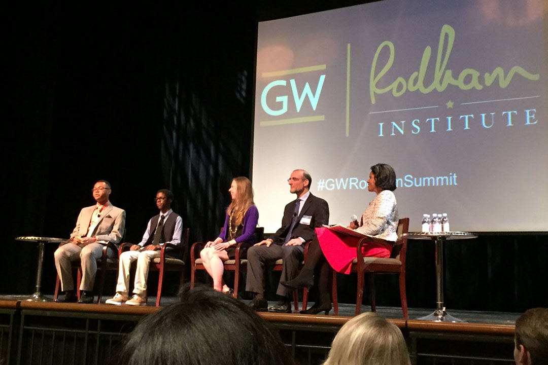 "A group of five panelists including Chelsea Clinton sit on a stage with the words ""GW"" and ""Rodham Institute"" behind them."